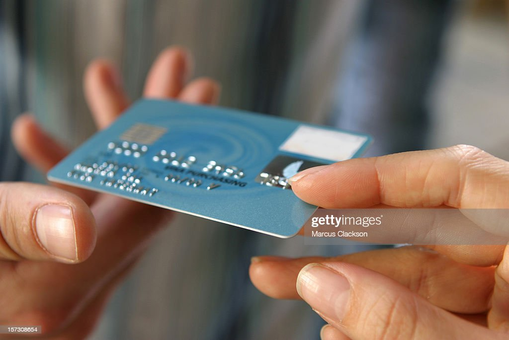Hand passing a payment card (N.B. Mocked up details*)