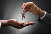 Close-up Of Hands Giving Keys Of An Apartment Against Gray Background