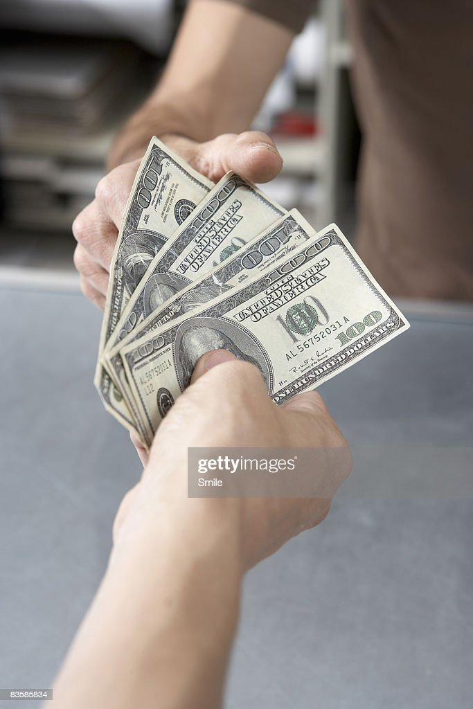 hand passing over cash to another hand : Stock Photo