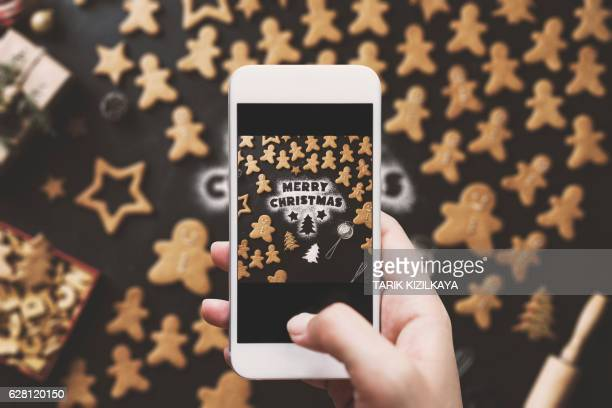 Hand photographing, Christmas gingerbread men cookies table top