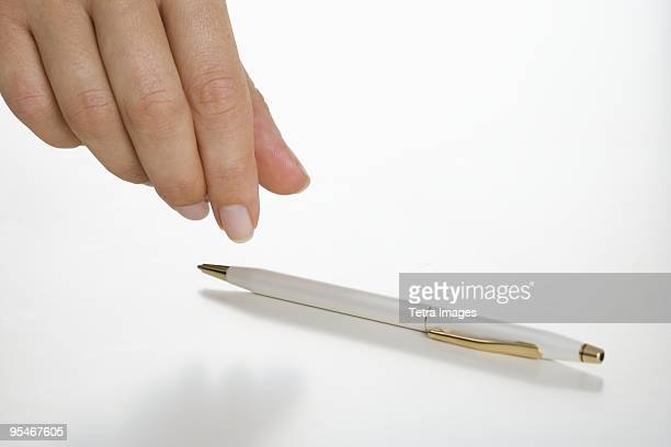 Hand picking up a pen