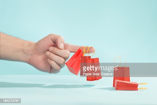 Hand picking up tiny shopping bags on finger