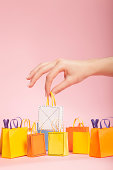 Hand picking up white tiny paper shopping bag