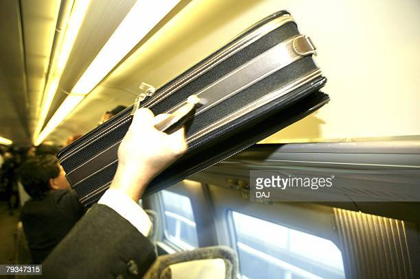 Hand placing baggage in overhead storage on train