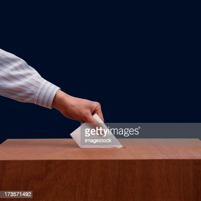 Hand placing ballot paper into wooden box