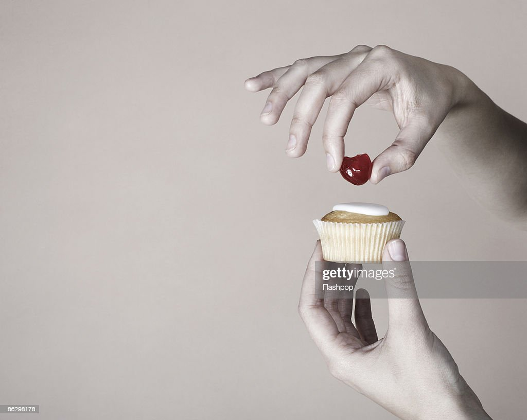 Hand placing cherry on top of cup cake : Stock Photo