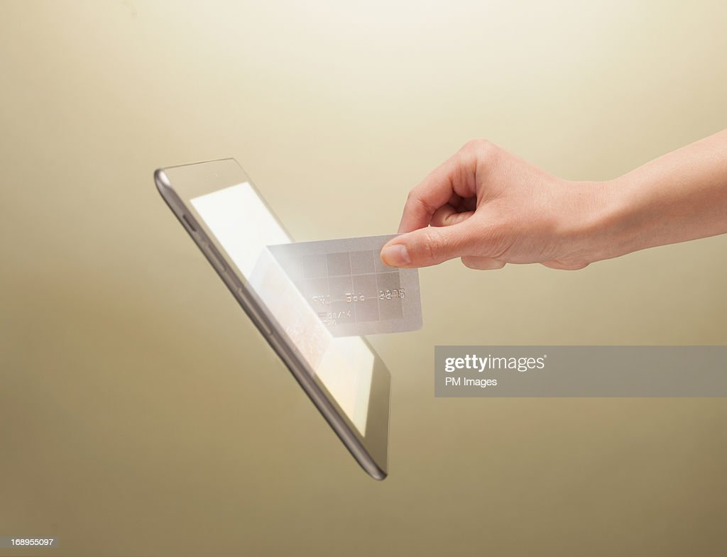 Hand placing credit card into tablet : Stock Photo
