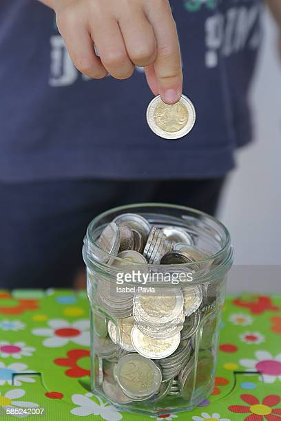Hand Placing Euro in Jar