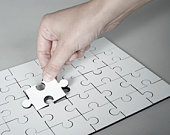Hand placing last piece into jigsaw puzzle