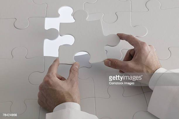 Hand placing puzzle piece into jigsaw puzzle