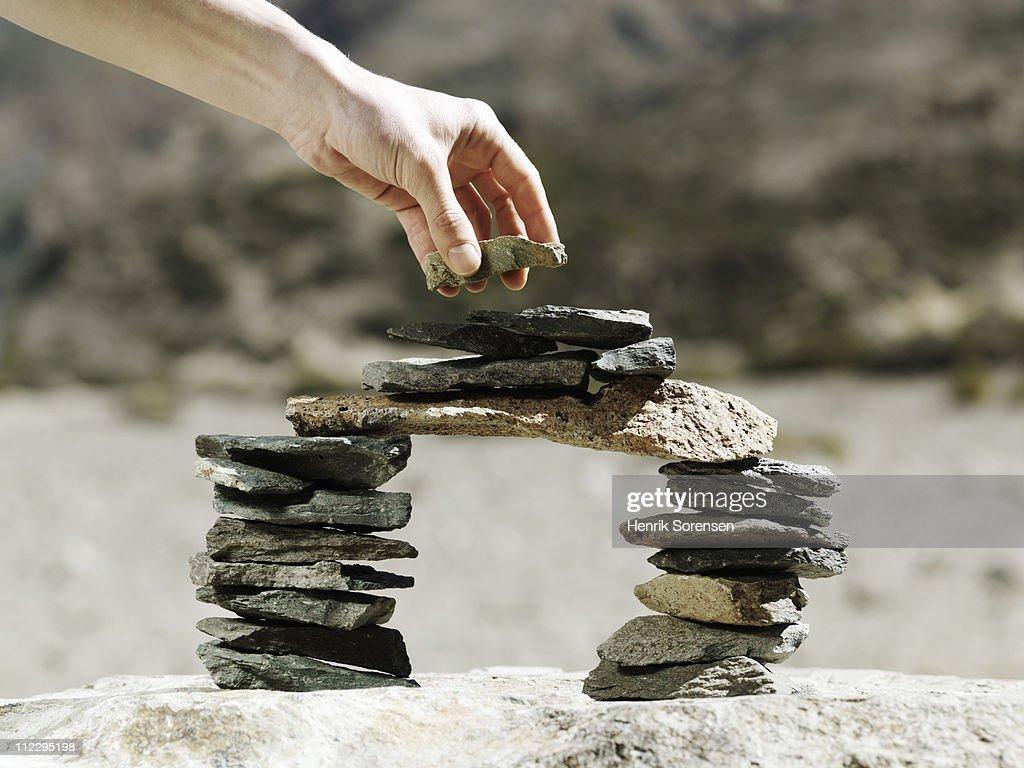 Hand placing stone on balancing rock bridge