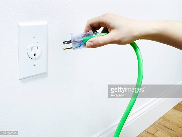 Hand plugging green power cord into outlet.