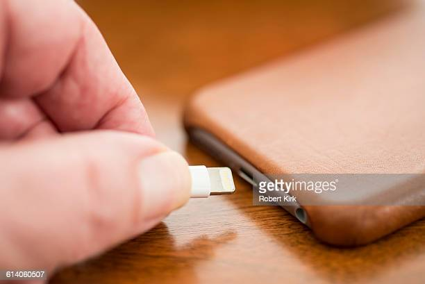 Hand plugging in phone charger
