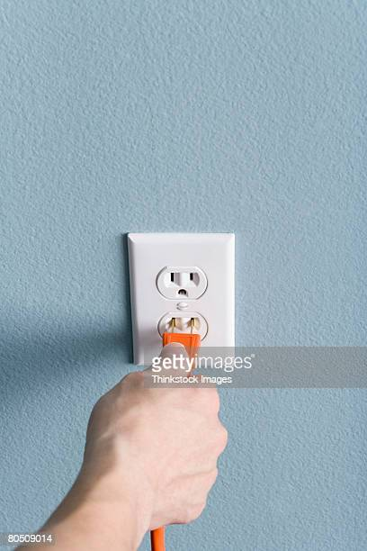 Hand plugging power cord into outlet