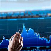 Hand pointing at financial graph, studio shot