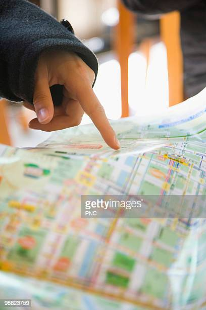 Hand pointing at map