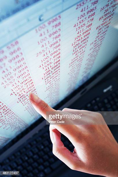hand pointing at numbers on computer screen