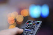 Hand pointing remote at television