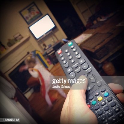 Hand pointing remote control towards television : Stock Photo