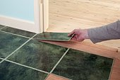 Hand positioning piece of green marble effect tile at corner of door and skirting board in house