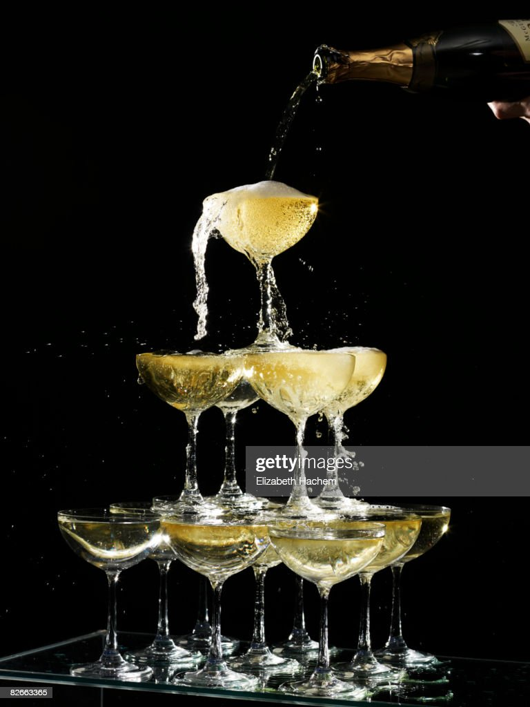 Hand pouring a champagne fountain