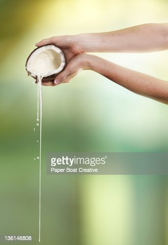 hand pouring coconut milk out of a mature coconut