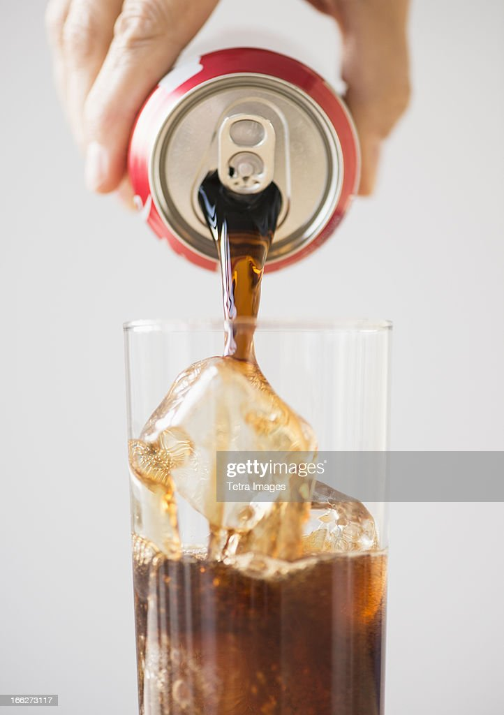 Hand pouring cola