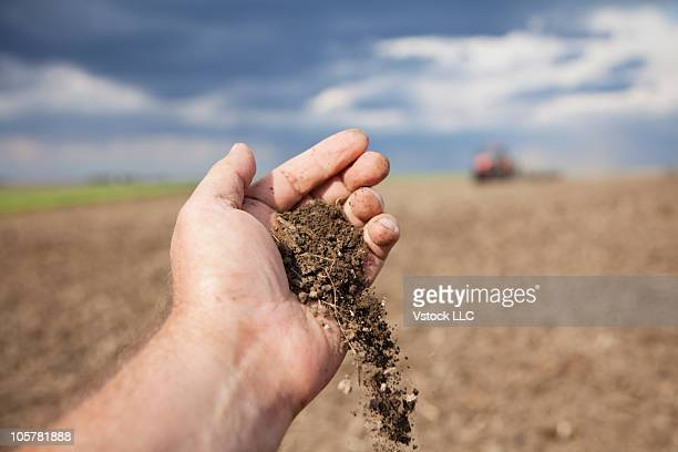 Hand pouring dirt onto ground