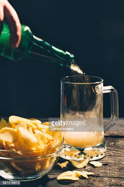 Hand pouring glass of beer near potato chips