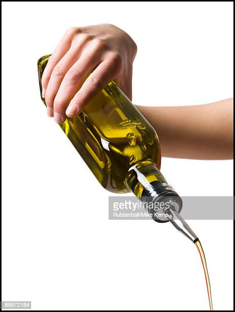 hand pouring olive oil