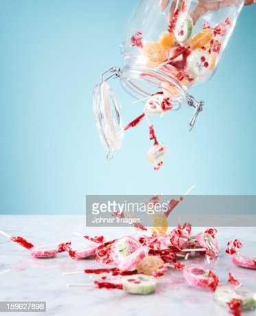 Hand pouring small lollipops from jar