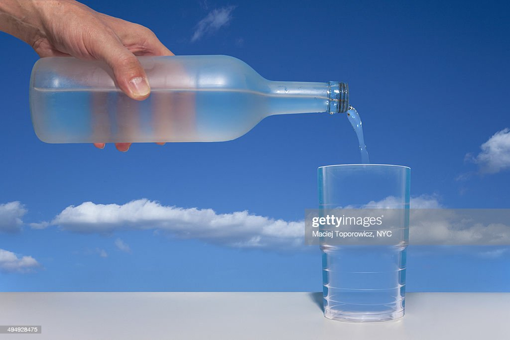 Hand pouring water from a bottle against blue sky : Stock Photo