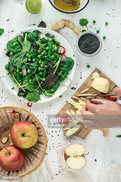 Hand preparing salad cutting apple