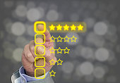 Hand pressing yellow five star button of performance rating on dark background with bokeh