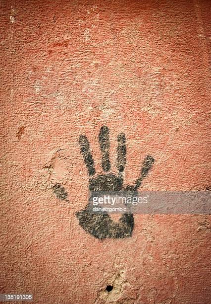 Mão impressão sobre a parede com um Buraco de Bala.