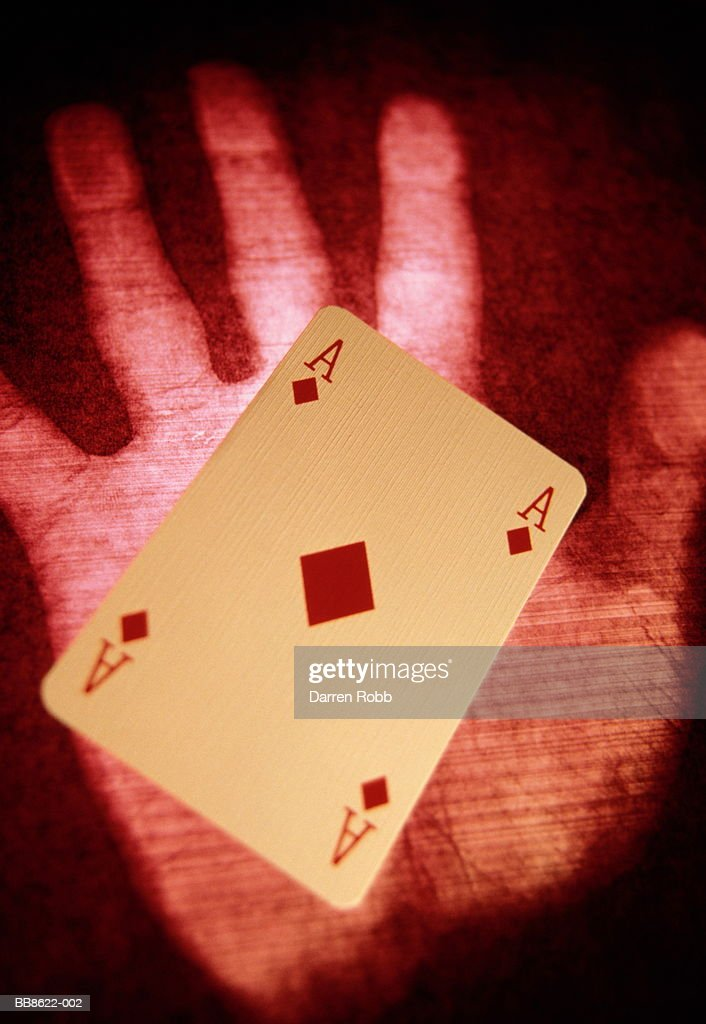 Hand print with playing card on palm, close-up, montage