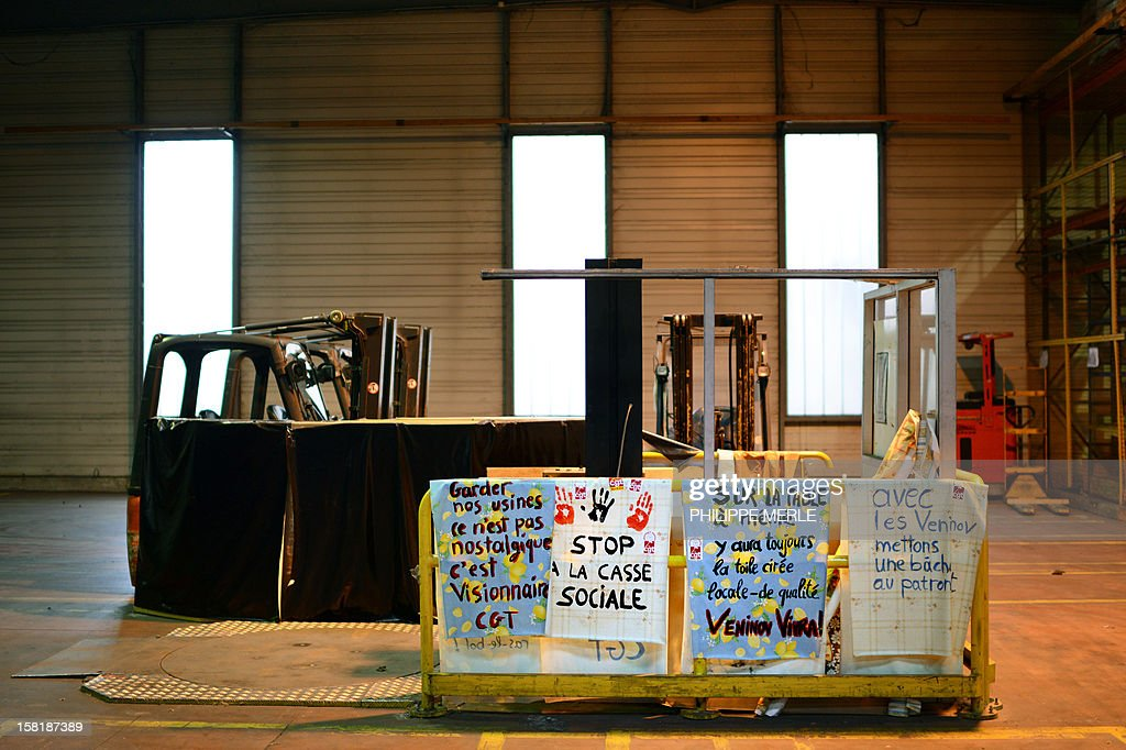 Hand printed signs are pictured at the Veninov plant, European leader in table covering manufacturing, in Venissieux, near Lyon on December 10, 2012. Veninov's workers have occupied their plant today demanding that the new owners, Austrian outfit Windhager, restart machines as soon as possible.