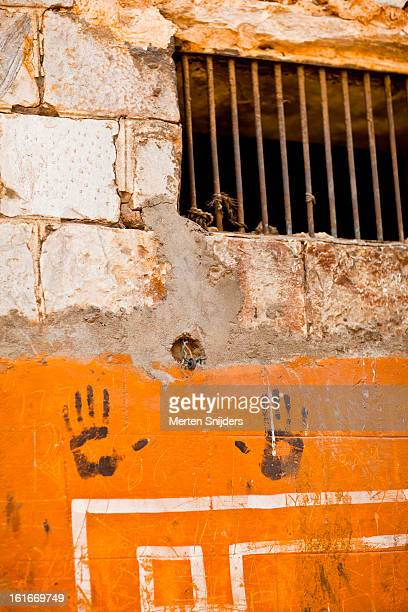 Hand prints on corroded orange wall