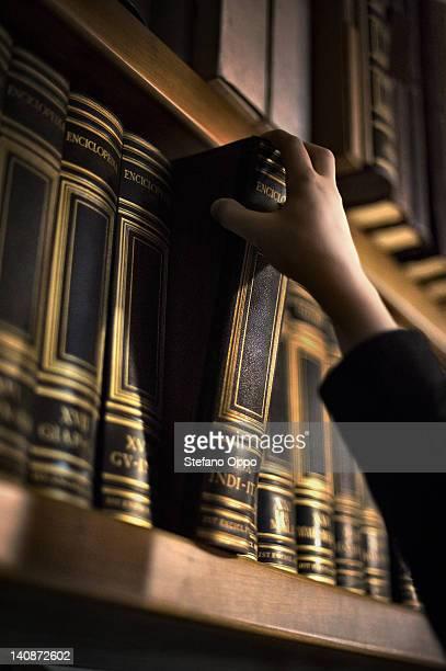 Hand pulling book from bookshelf