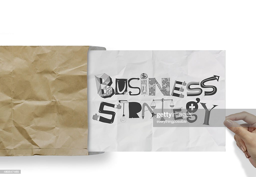 hand pulling crumpled paper from envelope with design word BUSIN : Stock Photo