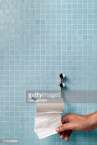 Hand pulling last square of toilet paper from the roll