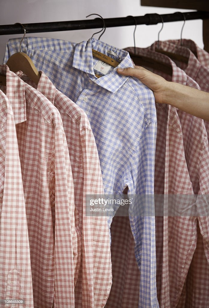 A hand pulling out one blue shirt amongst red ones : Stock Photo