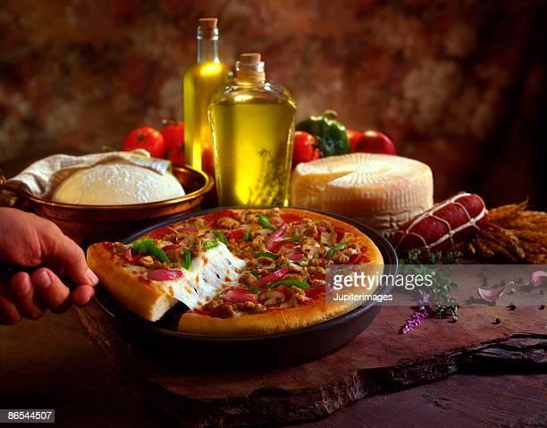 Hand pulling slice from pizza still life