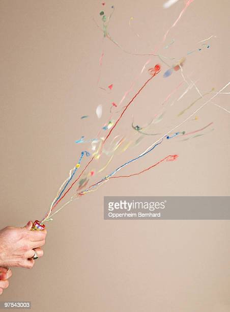 hand pulling string of party popper