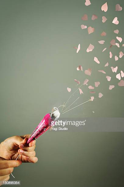 hand pulling string of party popper,Heart