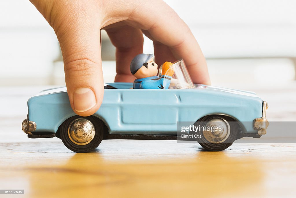 Hand pushing vintage blue toy convertible car : Stock Photo