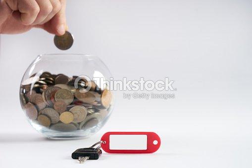 hand legen geld auf glas sparschwein mit m nzen gef llt stock foto thinkstock. Black Bedroom Furniture Sets. Home Design Ideas