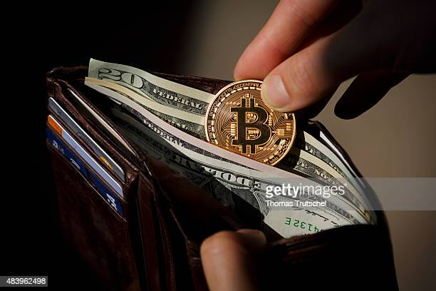 A hand puts a Bitcoin in a wallet filled with dollar bills on August 14 in Berlin Germany