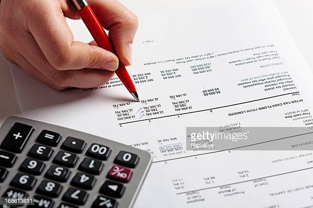 Hand puts check marks on financial document, calculator standing by