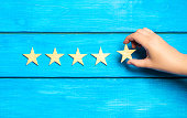 hand puts the fifth star. Quality status is five stars. A new star, achievement, universal recognition.The critic determines the rating of the restaurant, hotel, institution. Quality mark.
